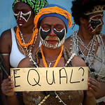 "Image of Papuan resident holding handmade sign reading ""EQUAL?"""