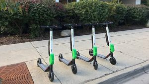 Four lime scooters parked on a sidwalk.